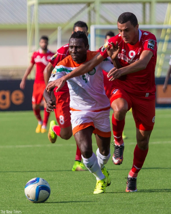 Niger's defender Musa Shehu (L) vies for the ball with Tunisian striker Ahmed Akaichi. Tunisia won 5-0 at Kigali Regional Stadium. (Timothy Kisambira)