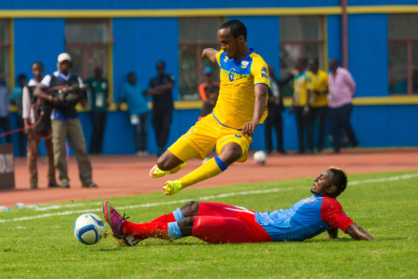 Amavubi's mid-fielder Yannick Mukunzi  jumps to avoid a tackle from a Congolese defender. (Timothy Kisambira)