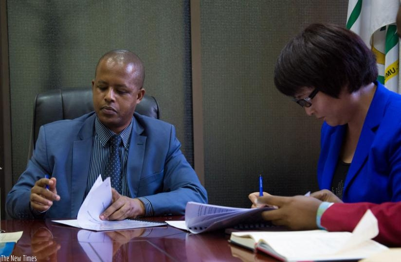 The Director General of Workforce Development Authority, Jerome Gasana (L), and Ann Xoi Wey, the acting general manager of C&H Garments, sign an agreement paperwork in Kigali yesterday. (Timothy Kisambira)