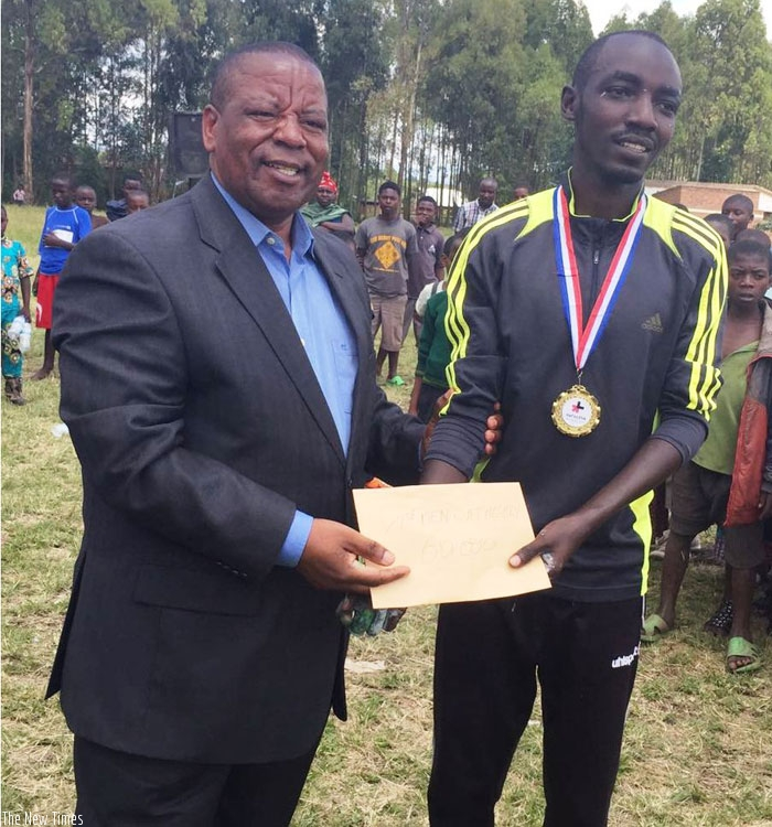 Nizeyimana (L) receiving the winner's prize from the Governor  of Nothern Province,  Aime Bosenibamwe. (G. Assimwe)