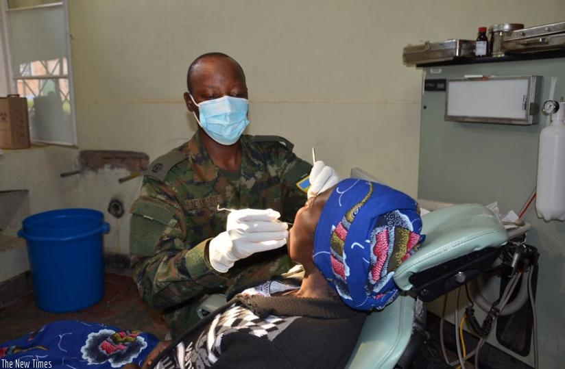 An army officer attends to a patient during the Army Week campaign in Muhanga District. (Frederic Byumvuhore)