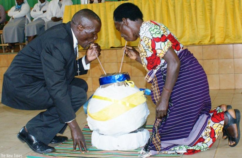 A Genocide survivor (R) shares a traditional brew with her former termentor, Aphrodis Kanani, from the same calabash after forgiving him. (Frederic Byumvuhore)