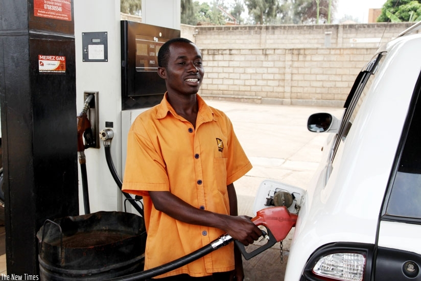 A pump attendant refills a car. Fuel pump prices have increased to Rwf 860 (File)