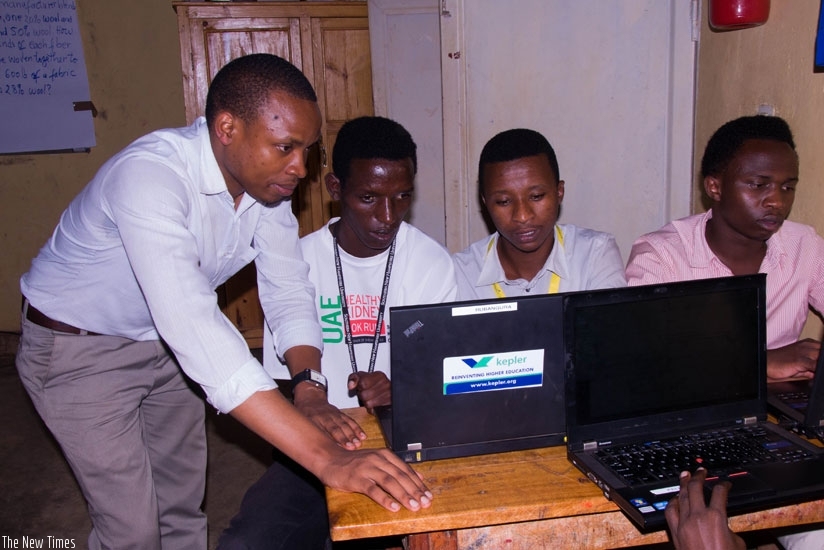 An instructor at Kepler Kiziba helps the students with computer work. (Teddy Kamanzi)