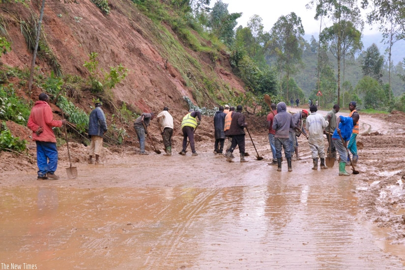 People clear muck from a road in Gakenke. (Teddy Kamanzi)