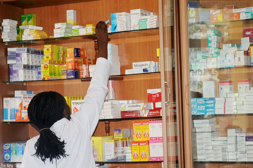 A pharmacist selects drugs from the shelf. (File)