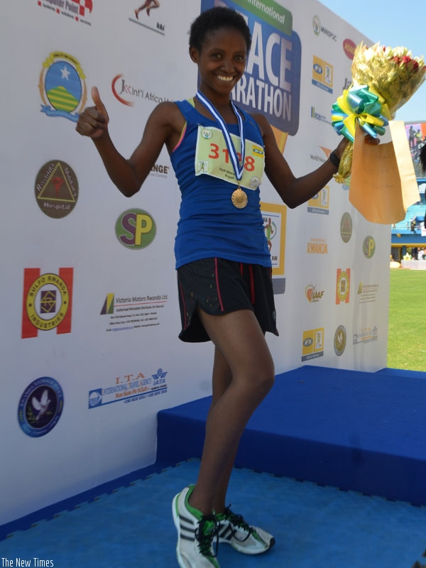 Salome Nyirarukundo celebrates her second position finish in the Kigali International Peace Marathon on Sunday. She has now set her sights on the Rio Olympic games. (S. Ngendahimana)