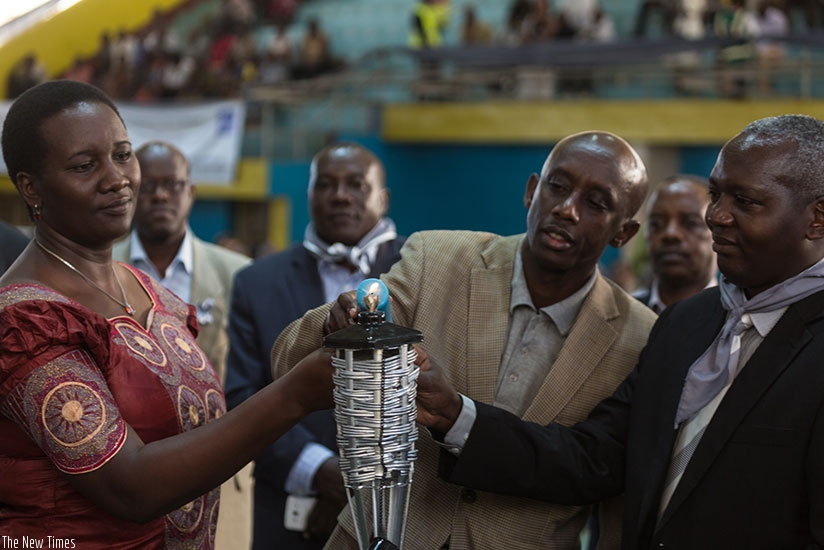 (L-R) Ministers Julienne Uwacu, Francis Kaboneka and Edouard Munyamariza, chairperson of Rwanda Civil Society Platform, light a flame during commemoration of over 100 employees of civil society organisations that perished in the Genocide. (Timothy Kisambira)