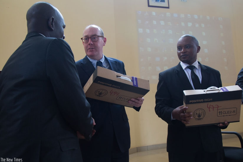 Ted Maly, the Unicef country representative (C) hands over a laptop to Jean Damascene Usabyimana, the Sector Education Officer for Gahanga in Kicukiro District (L), as the Minister for Primary and Secondary Education, Olivier Rwamukwaya, looks on yesterday. (Timothy Kisambira)