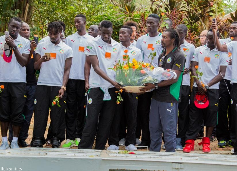 Team captain Cheikhou Kouyate and head Coach Aliou Cisse lead the team to lay a wreath on one of the mass graves at Gisozi Genocide Memorial. (F. Niyigena)