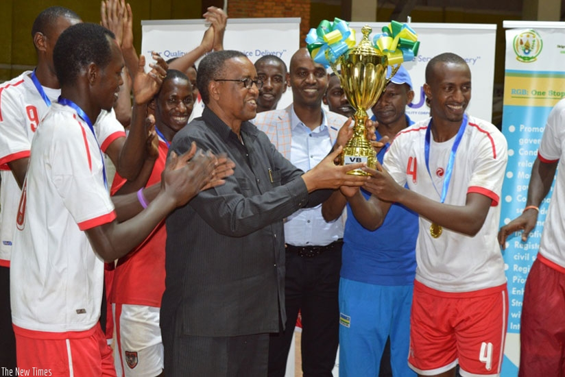 INATEK Vice Chancellor Prof. Silas Lwakabamba (C) lifts the Genocide Memorial Volleyball tournament trophy as players cheer on. (Geoffrey Asiimwe)
