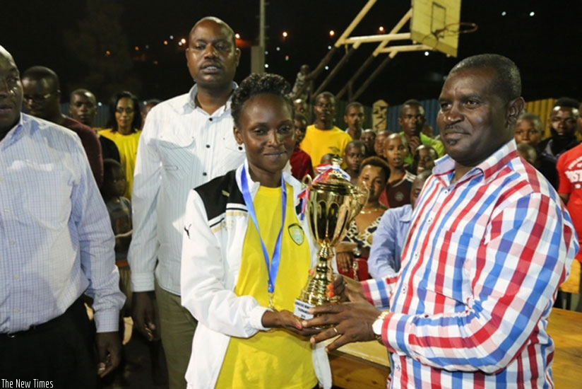 Gorillas captain Gatesi Confiance recieves the the trophy from Emmanuel Bugingo Director of Sports in the Ministry of Sports and Culture. (Geoffrey Asiimwe)