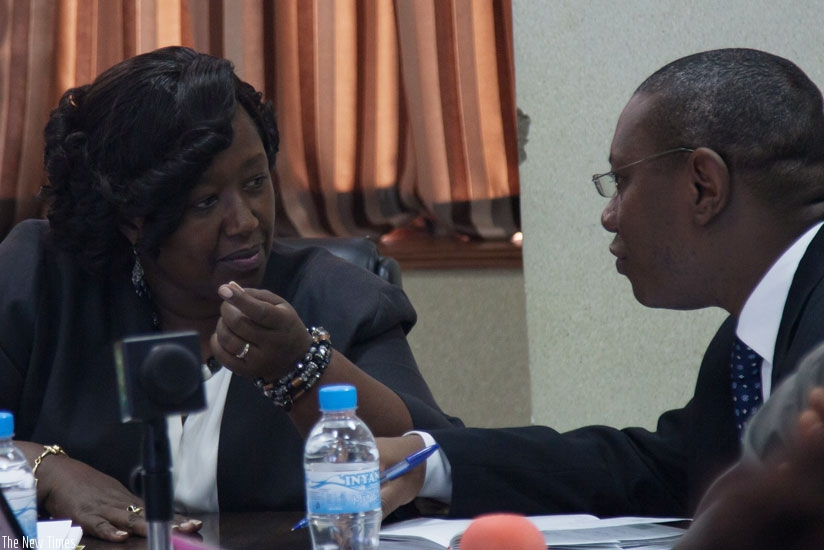 Minister Binagwaho (L) consults with Dr Patrick Ndimubanzi,  the State Minister in charge of Public Health and Primary Health Care, during the news conference in Kigali. (Nadege Imbabazi)
