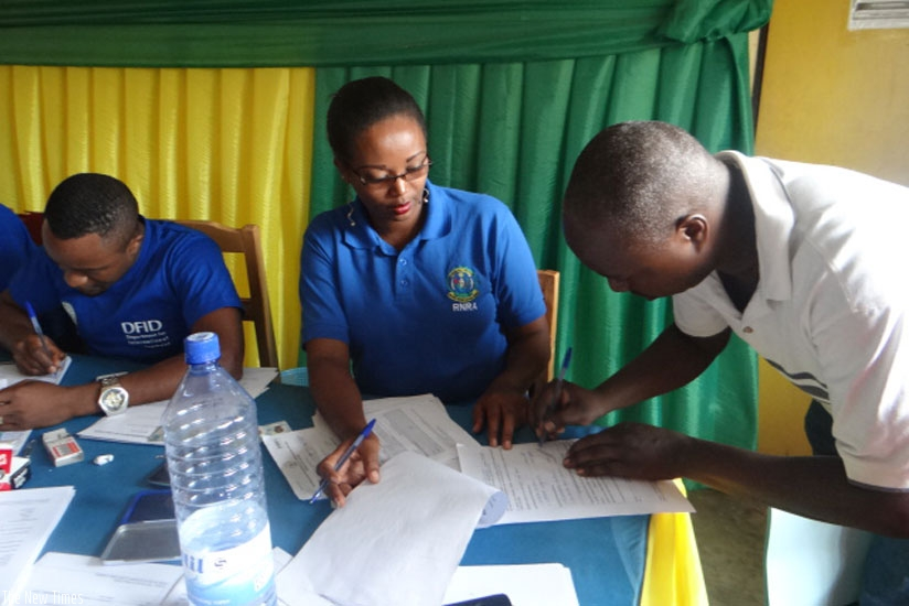 Land registration officers help Kamonyi residents register their property in order to get land titles. (Frederic Byumvuhore)