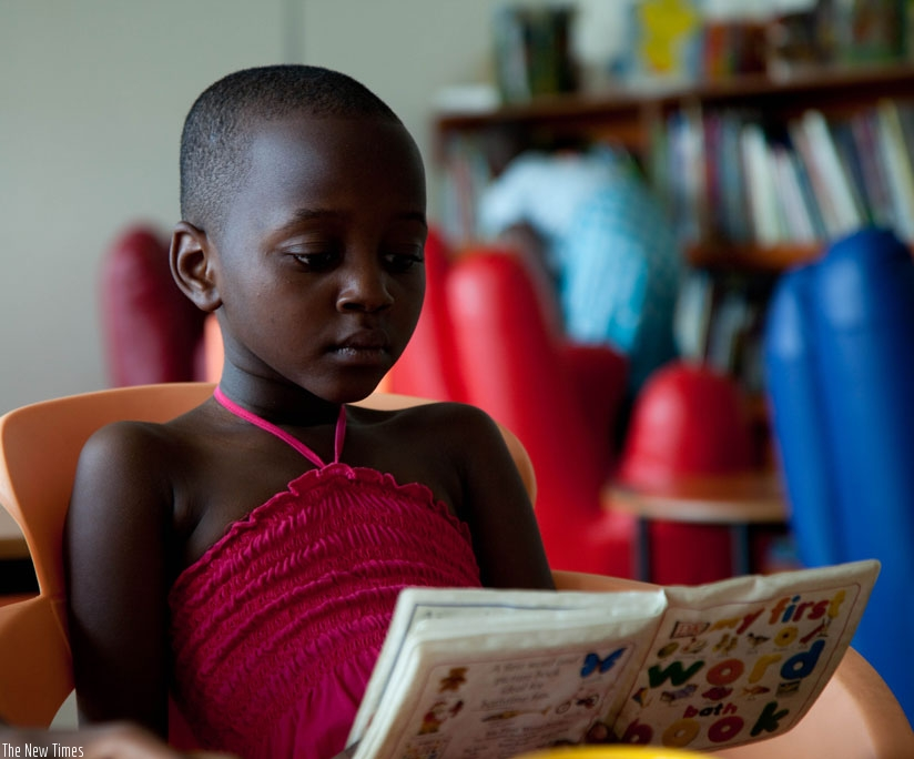 A child reads a book at the Kigali Public Library. (T.Kisambira)