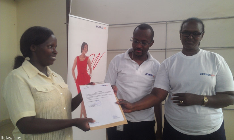 Employees of Access Bank giving document of payment confirmation to Genevieve Uwamahoro, the Executive Secretary of Nyarugunga Sector. (Frederic Byumvuhore)