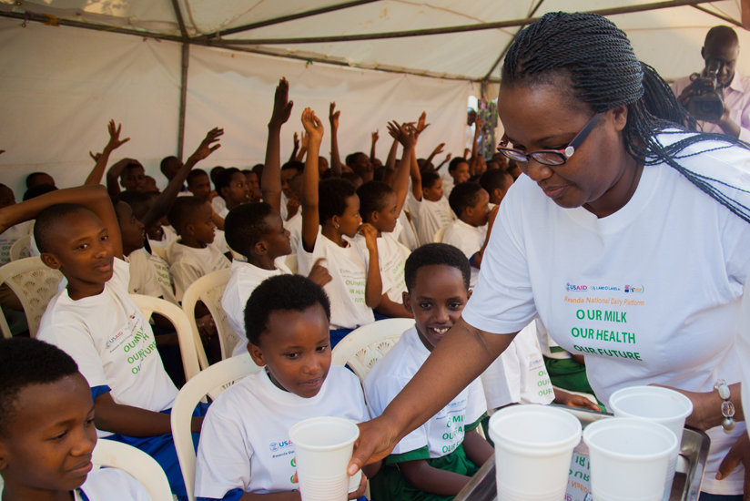 Mukeshimana serves milk to schoolchildren during the launch of the campaign to raise awareness of the importance of drinking milk in Kigali yesterday. (Nadege Imbabazi)