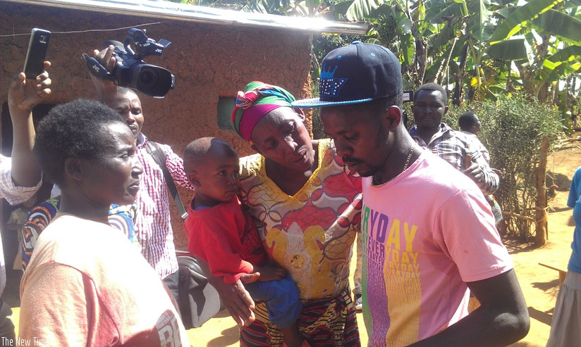 Ngendahimana is consoled by his mother (2nd R) as he arrives at home. (Frederic Byumvuhore)