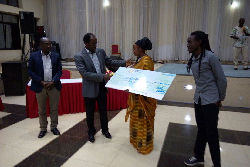 Ndayisaba hands over a cheque to Uwineza who emerged third in the song category. / Frederic Byumvuhore