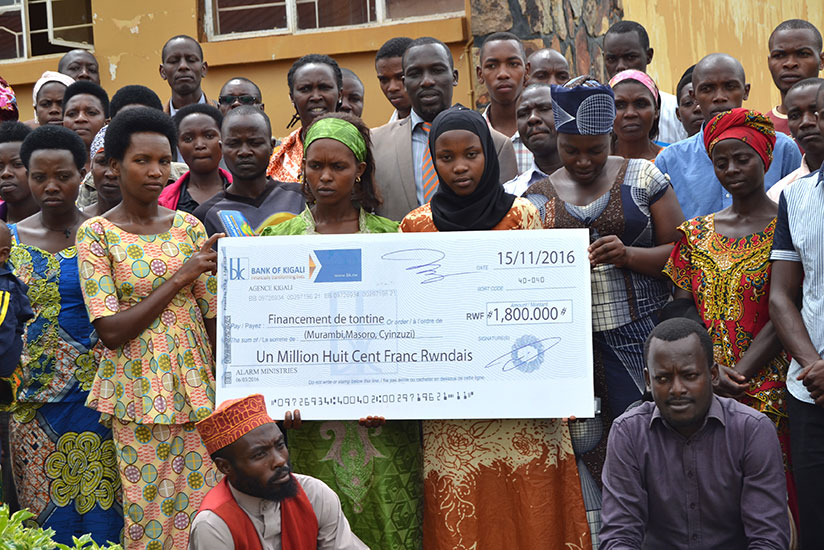 Some of the members of the women and youth savings groups pose with the dummy cheque of the donation. / Frederic Byumvuhore