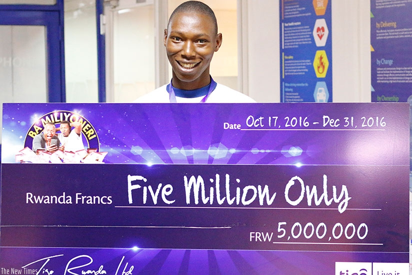 Simuganwa poses with a dummy cheque for his Rwf5m prize cash. (Courtesy)