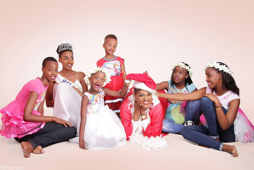 Miss Naiades 2016 Peace Kwizera Ndaruhutse (with crown) and gospel singer Aline Gahongayire, pose for a photo with some of the kids who will take part in the Christmas Kids festival. / Donata Kiiza