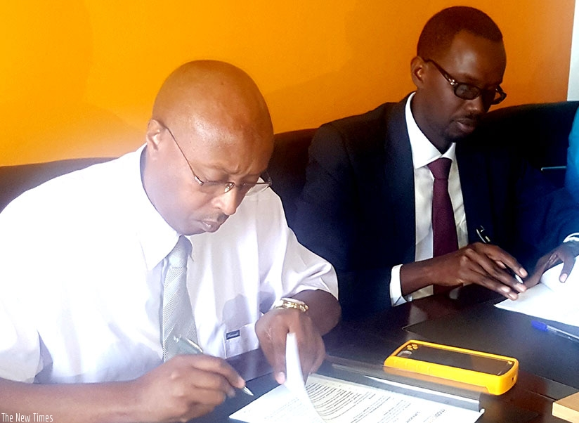 Nyagahene (left) and Barera sign the partnership deal at MobiCash offices in Gishushu. E-payment facilities, like POS, are supporting job-creation efforts. (Photos by Frederic Byumvuhore)
