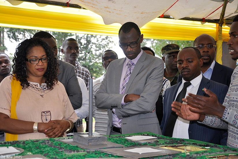 An exhibitor explains to MP Agnes Mukazibera (L) and Minister Musafiri (C) a concept at Ines Ruhengeri on Tuesday. (Frederic Byumvuhore)
