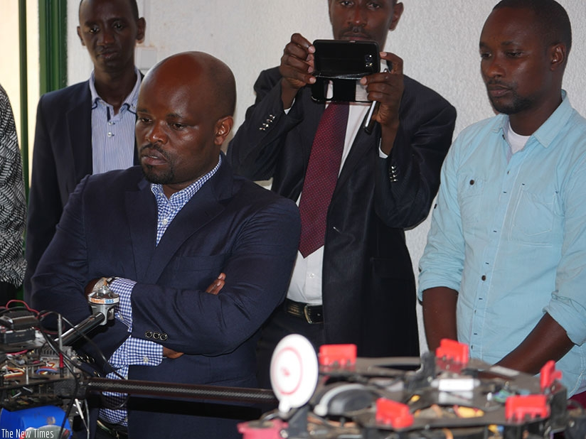 Minister Nsengimana (L) follows a demonstration of how the drone operates. (Photos by Frederic Byumvuhore)