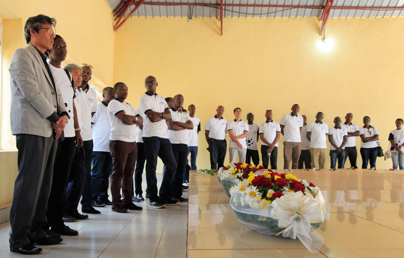 AOS Chief Executive Officer Dae Heak AN (L) and the staff observe a minute of silence to honor the victims at Rukara Genocide memorial on Friday