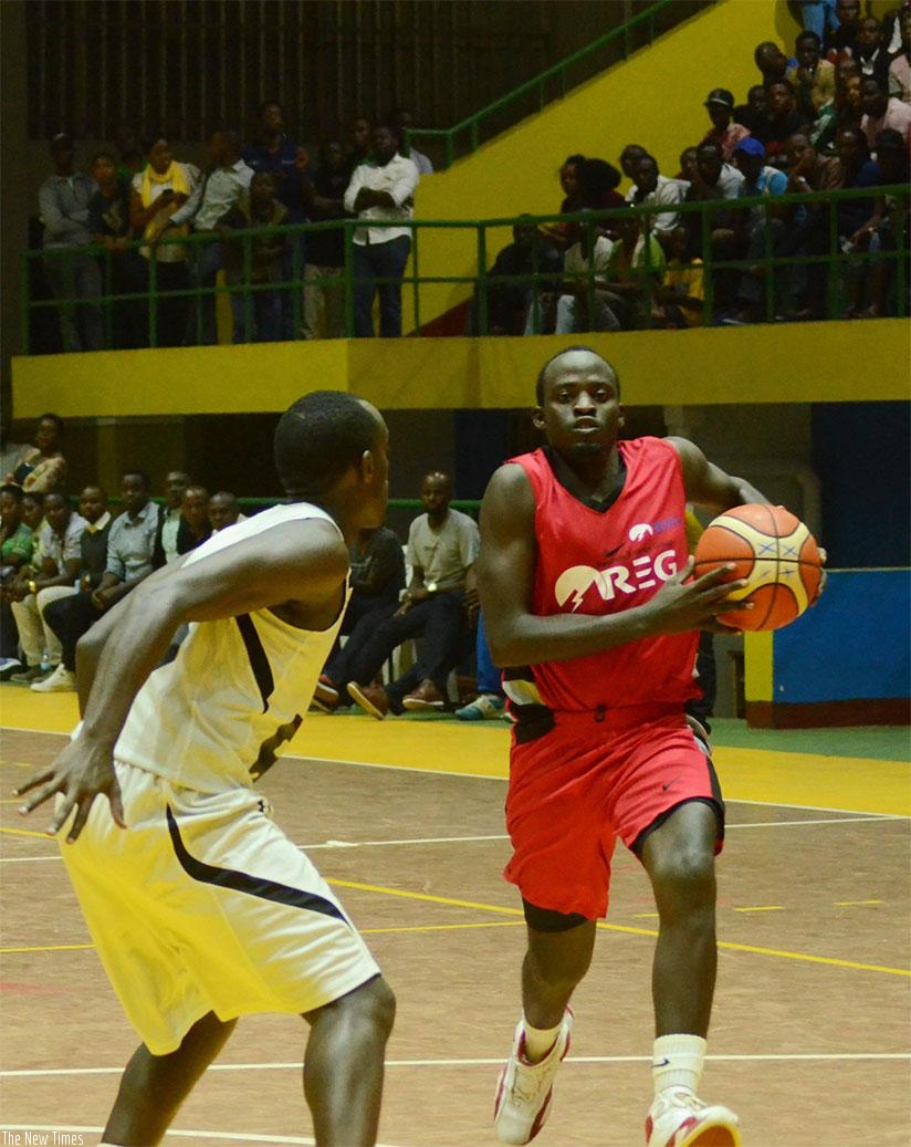 REG's Patrick Habiyambere tries to go past Patriot's Aristide Mugabe during the game one of the ongoing playoffs finals series at Amahoro indoor stadium. Sam Ngendahimana