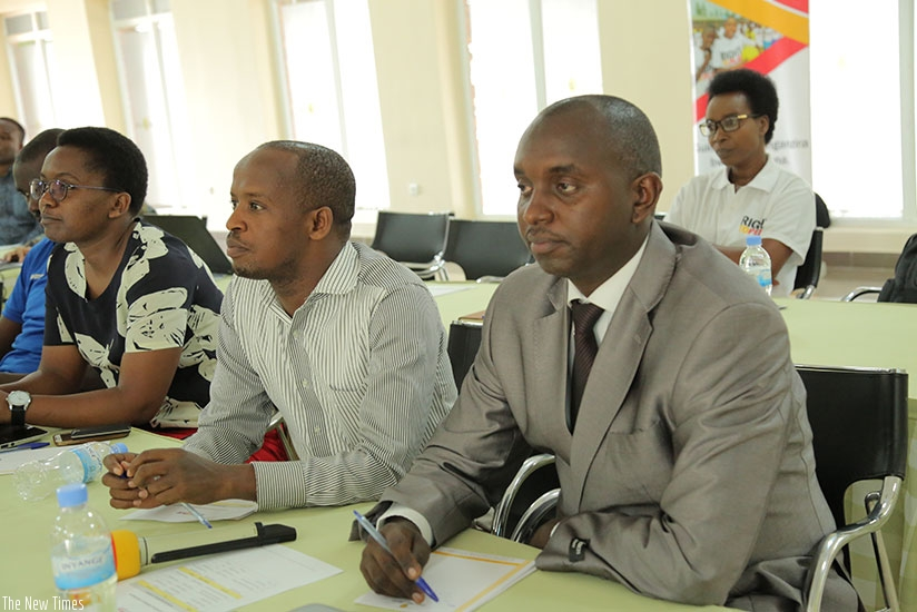 Participants follow proceedings at the conference.  (Francis Byaruhanga)