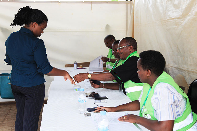 Volunteers check the passport of one voter before casting her vote in Kigali