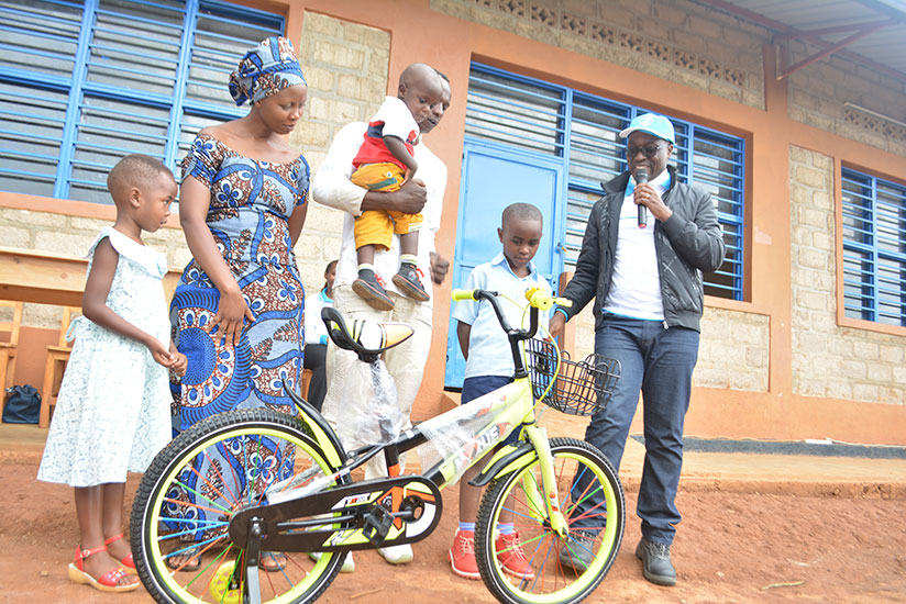 1510693665Eng.-Aime-Muzola,-Chief-Executive-of-WASAC-handing-over-a-bicycle-to-Rukundo-as-his-parents-look-on