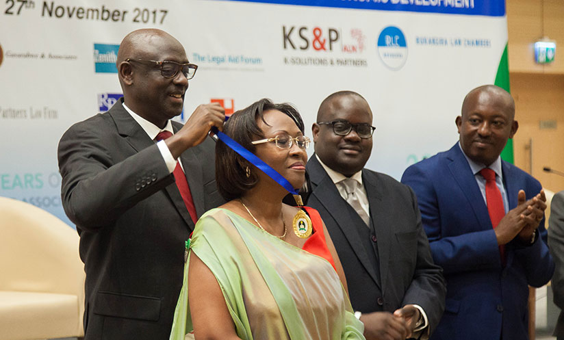 1511813403Minister-of-Justice-Johnston-Busingye-gives-the-medal-of-recognition-to-Me-Claudine-Gasarabwe-during-the-celebration-ceremony.-One-of-the-2-women-who-started-the-Bar-Association
