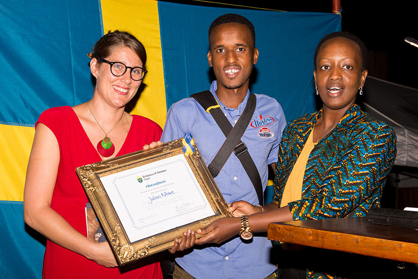 Sweden's envoy to Rwanda Jenny Ohlsson and PS at MIGEPROF Nadine Umutoni award Julius Ntare the winner of a photo-exhibition entitled 'Swedish Dads' and 'Rwandan Dads' that feature....