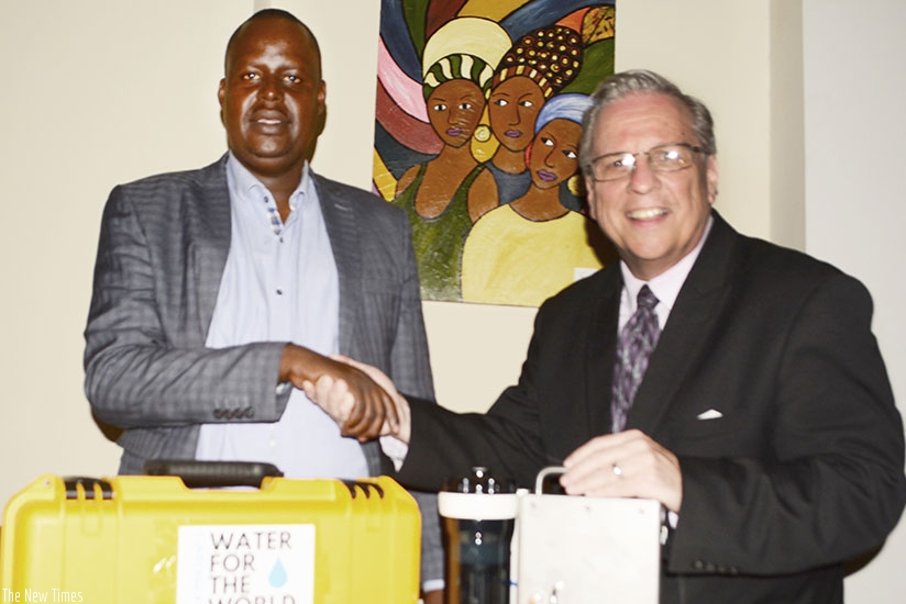 Thomas (right) hands over some of the equipment to Byiringiro in Kigali. / Frederic Byumvuhore.