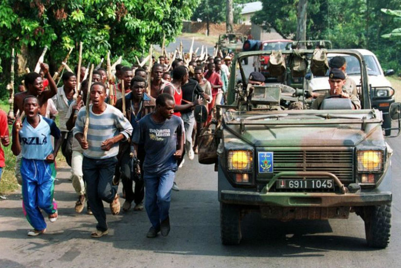 French soldiers, seen in this undated picture with members of the Interahamwe -- the pro-government militia that carried out most of the killings -- are accused of supporting the g....