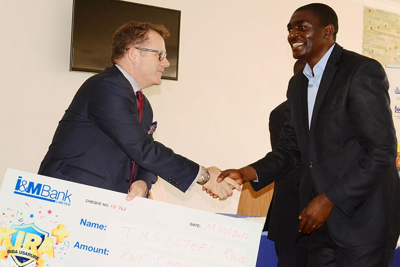 SteelRwa's Ndikubwimana (right) receives a dummy cheque of Rwf5m on behalf of the workers association, from Bairstow. / Frederic Byumvuhore.