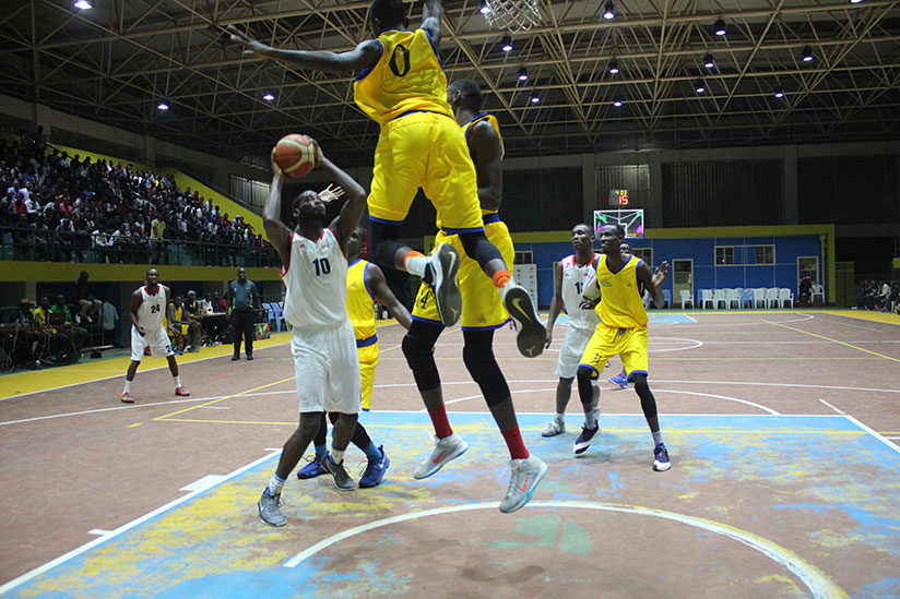 Power-forward Olivier Shyaka (#10) tries to overcome Gilbert Nijimbere (#0) for a two-pointer on Friday night. / Richard Bishumba