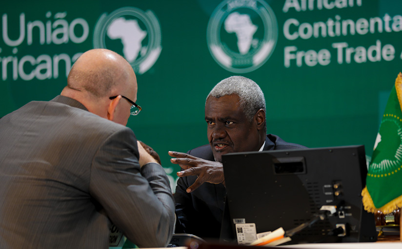 1521500717Chairperson-of-the-Commission-of-the-African-Union,-Moussa-Faki-Mahama-(R)-speaks-to-a-delegate-before-the-opening-session--of-the-meeting-of-the-Executive-council-of-ministers-of-Africa