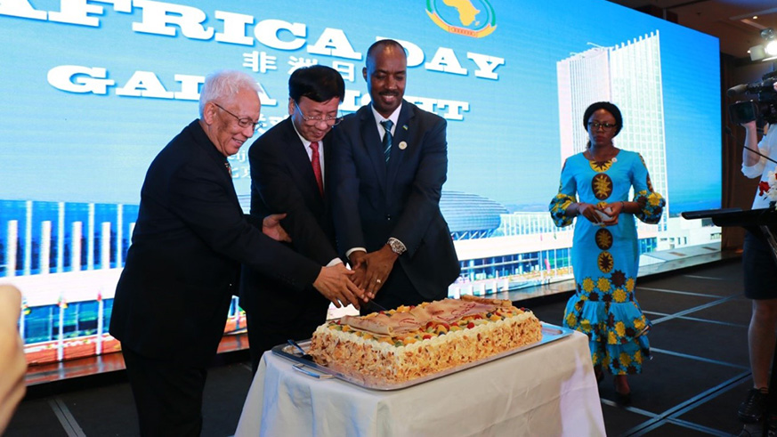 Amb. Kayonga (R) is joined by Victor Sikonina, the Ambassador of Madagascar and Dean of the African Diplomatic Corps (left) and Cao Jamming, the Vice Chairperson of the Standing Committee of China's National People's Congress to cut a cake in celebration of Africa Day. / Courtesy