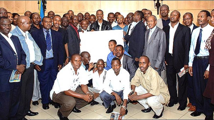 President Kagame (C) and Minister Nkusi (circled) pose for a photo with media managers and editors at Village Urugwiro on Tuesday after a two-day private meeting. The President received a birthday card from the media fraternity. (Photo/PPU)