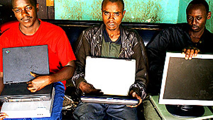 END OF THE ROAD: L-R: Sixbert Ngarukiyintwari, Erneste Niyonambaza aka Rubangura and Eric Manzi at Nyarugenge Police Station yesterday, with the laptops and other items they allegedly stole. (Photo/ G. Muramila)