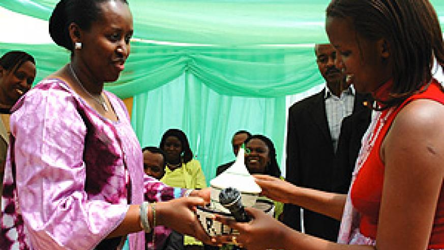 Mrs Kagame receives a gift from the Executive Secretary of Kicukiro Sector, Marie Rose Nirera, yesterday. (Photo/G. Barya)