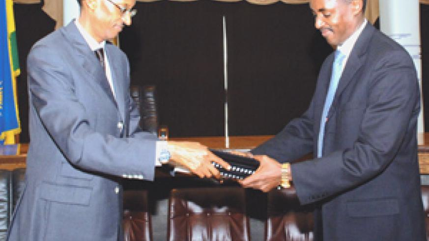 President Paul Kagame receives copies of the report from Jean de Dieu Mucyo, president of the Commission (Photo/PPU)