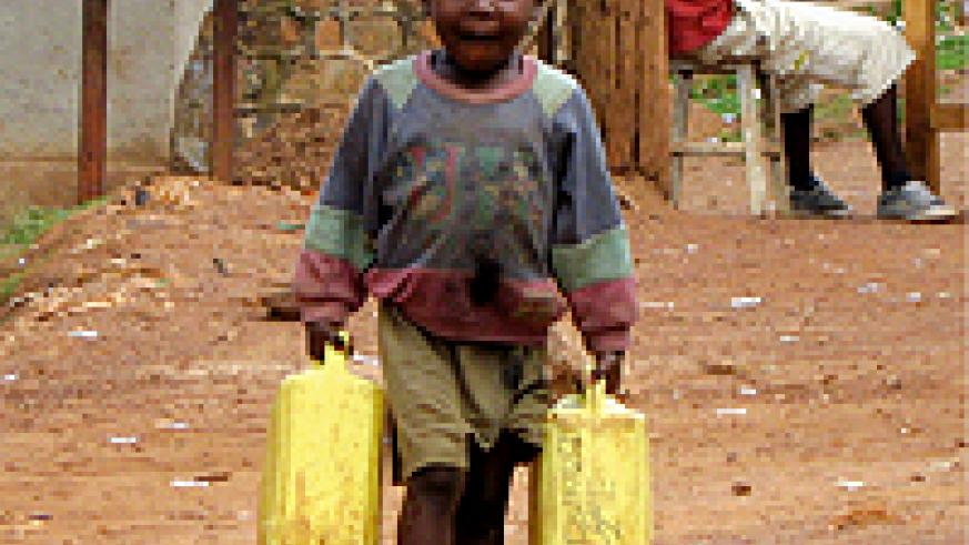 A young boy carries water in Kimisagara, a Kigali city suburb. (Photo/Pascal Manirakiza)