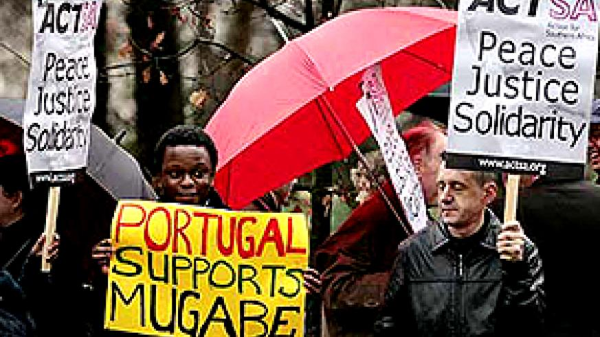 Pro-Mugabe supporters displaying placards on the streets of Lisbon, Portugal (Getty Images)