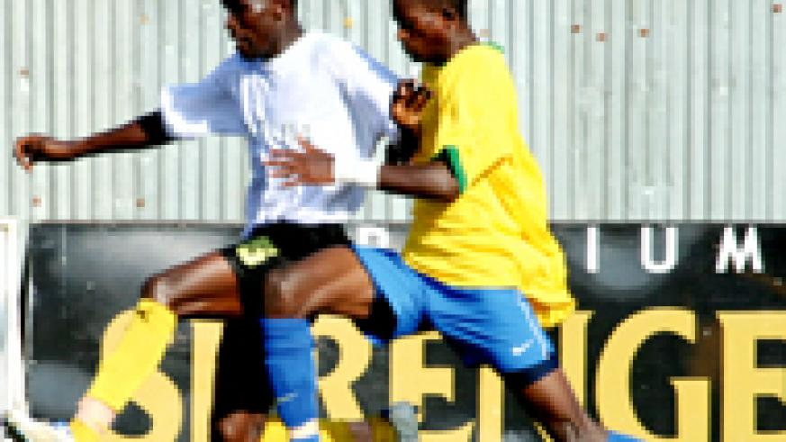 BATTLE: Rwanda's Donatien Tuyizere battles with Uganda's Vincent Kayiizi on Tuesday. Uganda won 2-0 but Rwanda out of disappointment whipped Dibouti 9-0 yesterday.