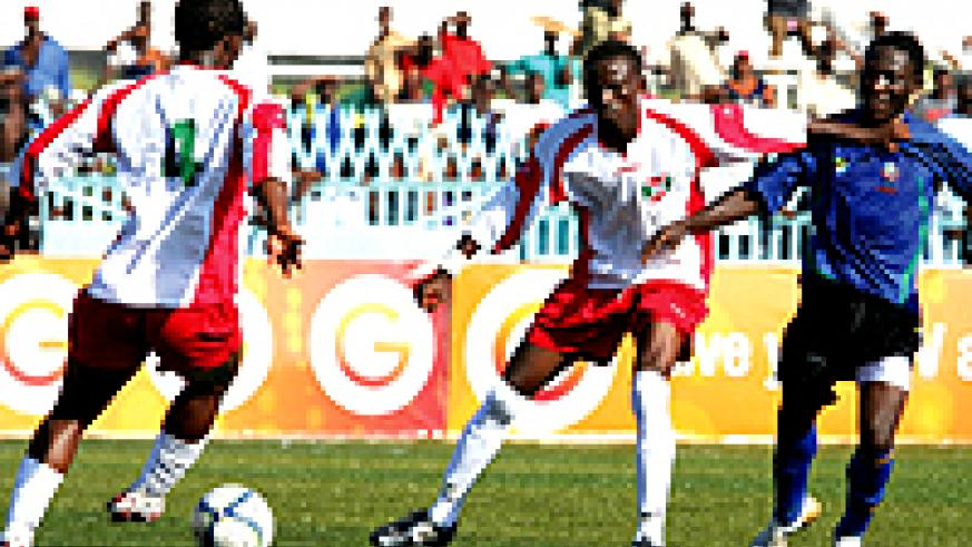 Burundi's Hussein Ndeyimana (left ) keeps the ball as team-mate Hassan Hakizimana shields away Tanzania's Danny Murwanda in Dar Saturday (Courtesy Photo)